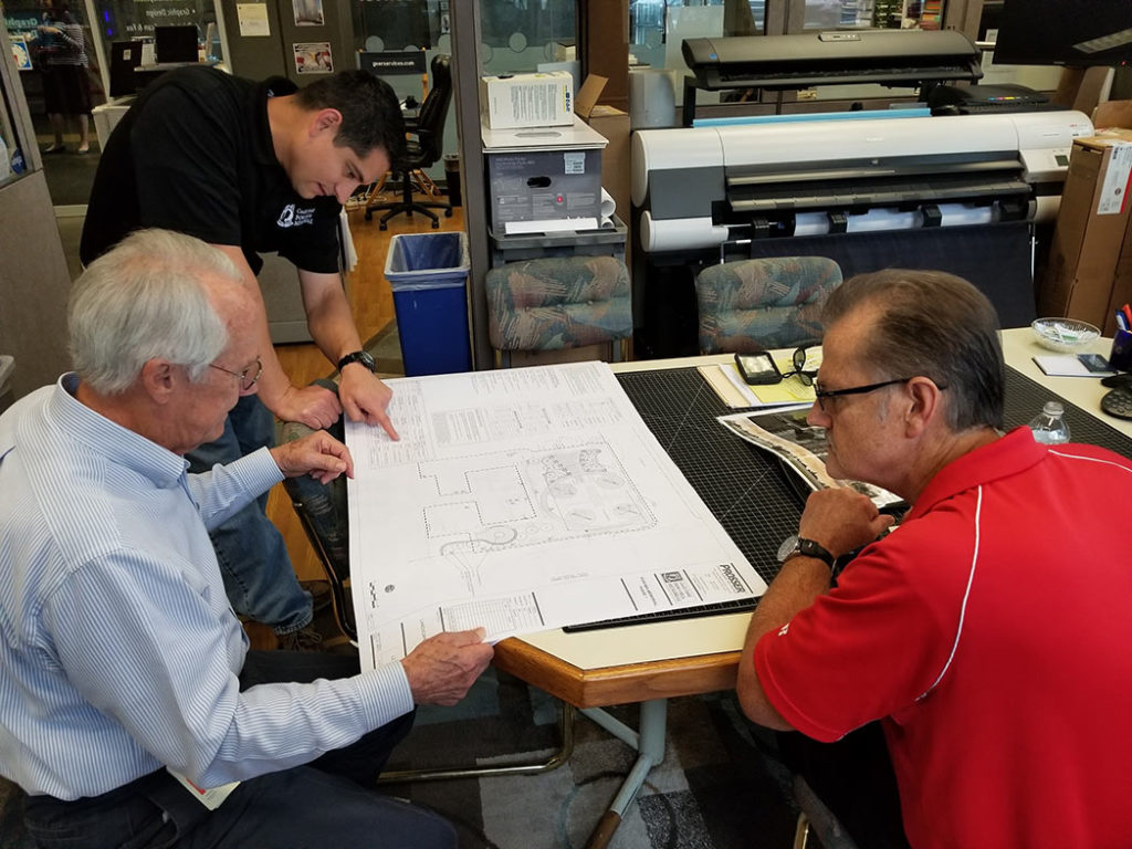 Mike Cassata (Cecil Field POW/MIA Memorial), Pat Geer and Jeff Strickland (Geer Services, Inc.) view the newly released plans and specifications provided by Prosser, Inc.